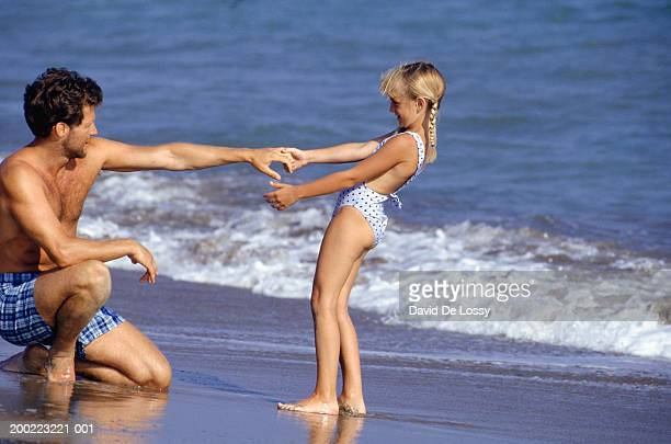 father and daughter (6-7) playing on beach - kin in de hand stock pictures, royalty-free photos & images