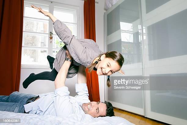Vater und Tochter spielen auf Bett