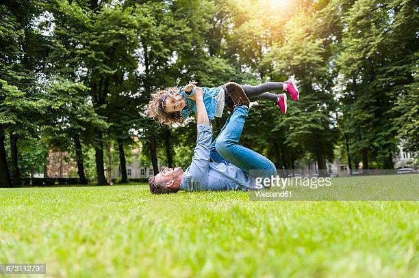 Father and daughter playing on meadow in park