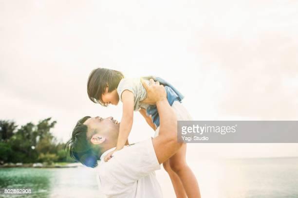 父と娘が浜辺で遊んで