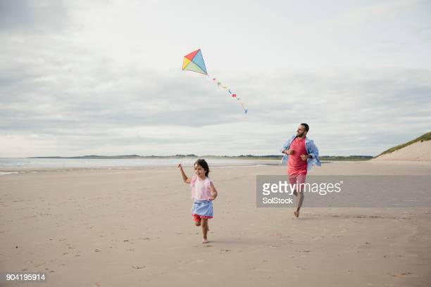 Father and Daughter Playing On The Beach With a Kite