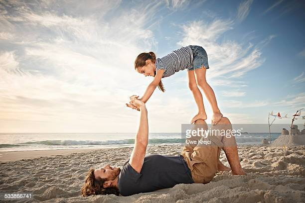 father and daughter playing - little girl laying on the beach stock photos and pictures