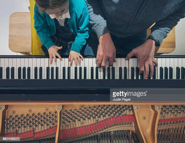 father and daughter playing the piano - duet stock pictures, royalty-free photos & images