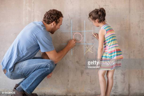 Father and daughter playing tic tac toe with chalk on a concrete wall