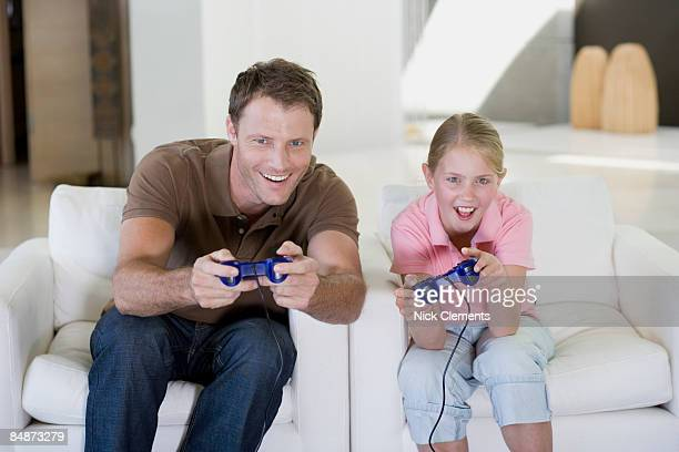 Father and daughter (8-9 yrs) playing video games