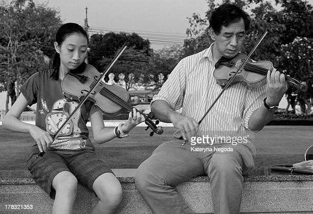 CONTENT] Father and daughter playing violins on the street in Bangkok Thailand Black and White