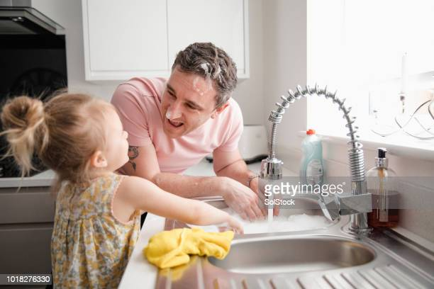 father and daughter playing with bubbles in the kitchen - kitchen sink stock pictures, royalty-free photos & images