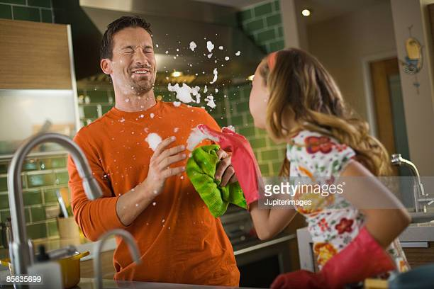 father and daughter playing with dishwashing bubbles - teasing stock pictures, royalty-free photos & images