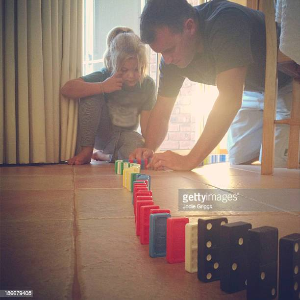 Father and daughter playing with dominoes on floor