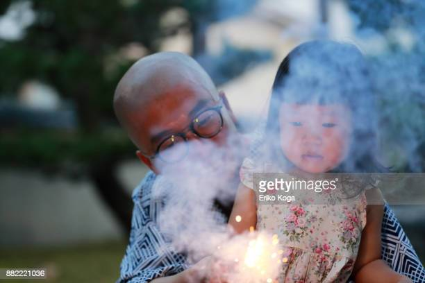 Father and daughter playing with fireworks