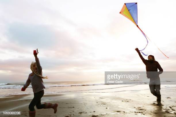 father and daughter playing with kite on beach - free stock pictures, royalty-free photos & images