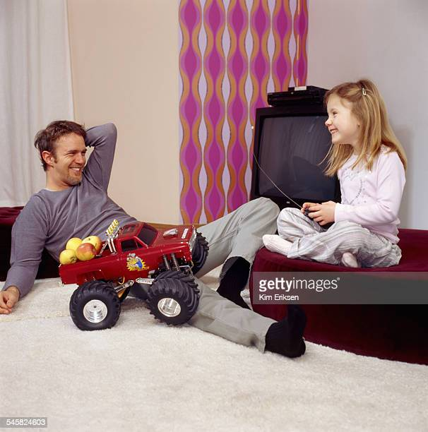 Father and Daughter Playing with Remote Controlled Truck