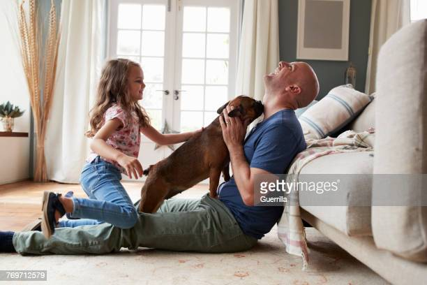Father and daughter playing with their pet dog at home