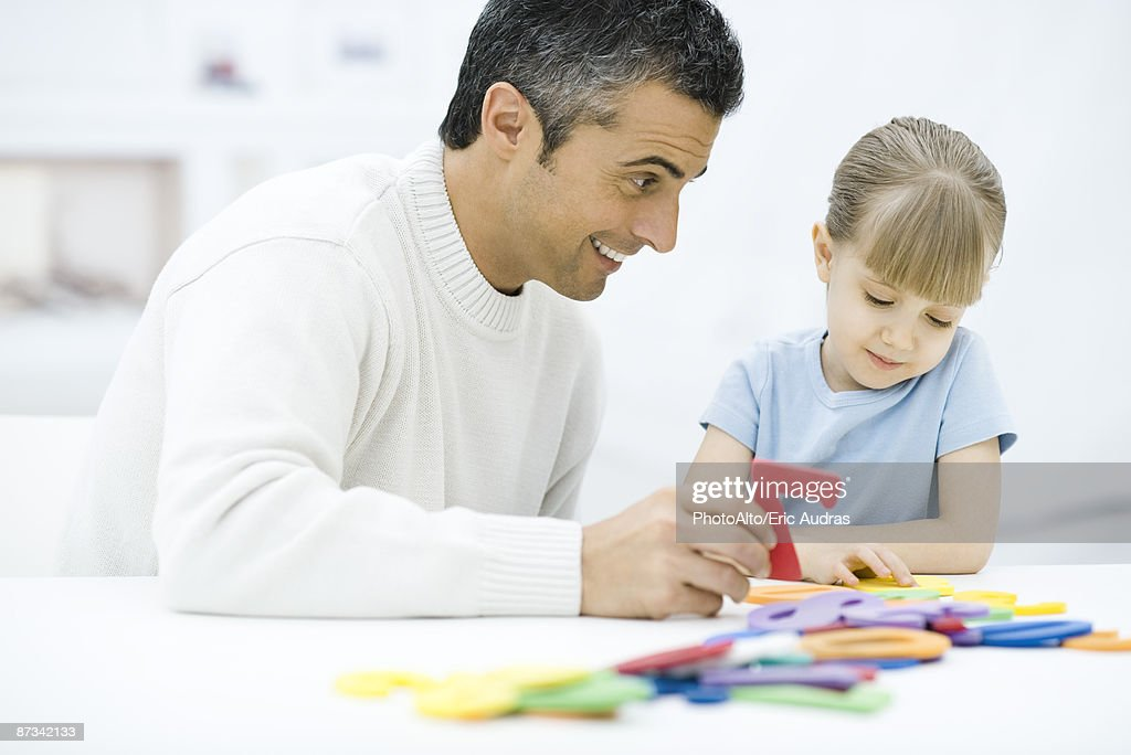 Father and daughter playing with toys together : Stock Photo