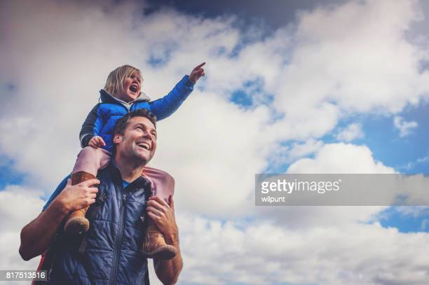 Father and Daughter Pointing Cloudy Sky