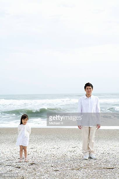 Father and daughter (6-7) posing on beach, portrait