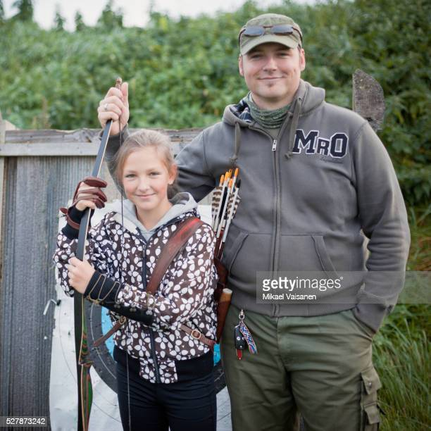 Father and daughter (10-12) posing with bow and arrow