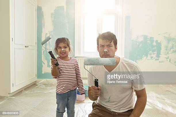 father and daughter posing with paint rollers - diy stock pictures, royalty-free photos & images