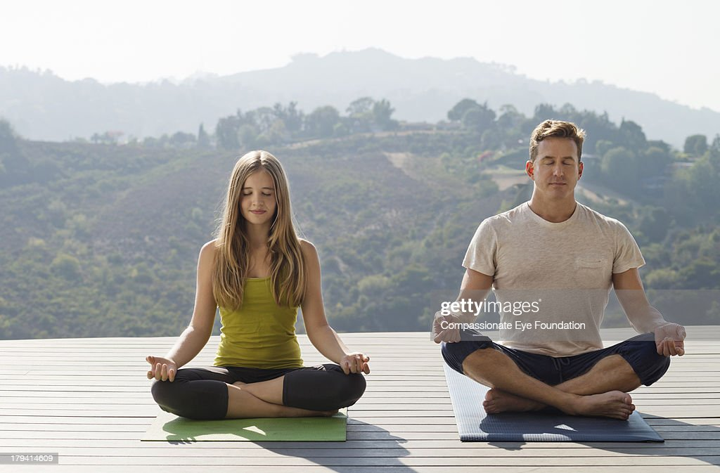 Father and daughter practicing yoga : Stock Photo