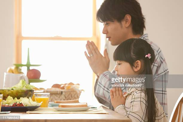 Father and Daughter Praying at Breakfast Table