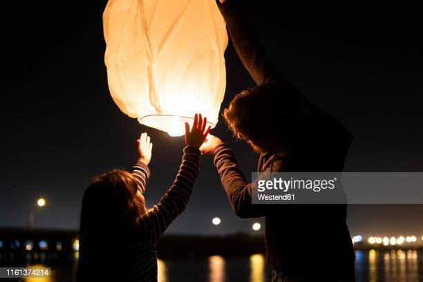 father and daughter preparing a sky lantern on the beach at night - ランタン ストックフォトと画像