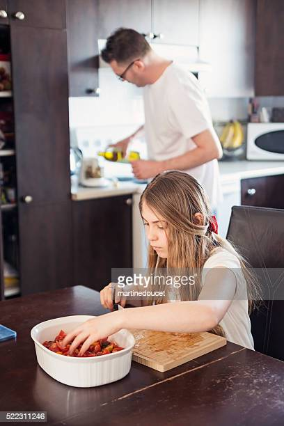 Father and daughter preparing food in home kitchen.