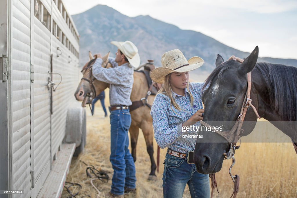 Father and daughter preparing the horses for an event in Utah, USA.
