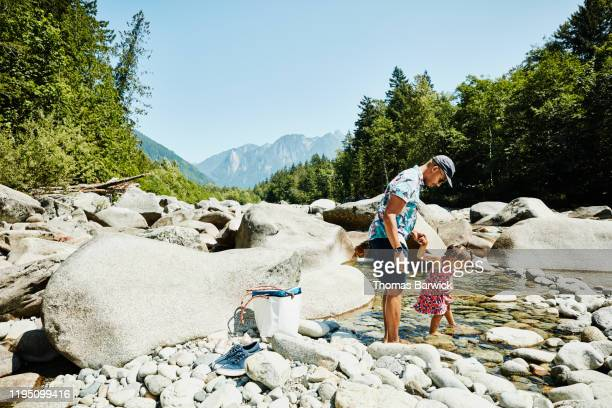 Father and daughter putting feet in river while having picnic during road trip