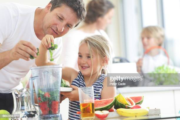 Father and daughter putting fruit into blender