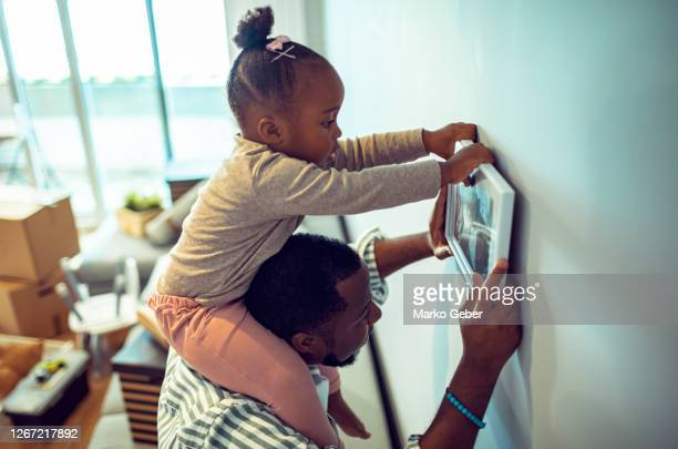 father and daughter putting up paintings in their new home - genderblend stock pictures, royalty-free photos & images