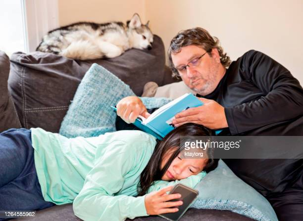 father and daughter read while quarantined at home - adoption stock pictures, royalty-free photos & images