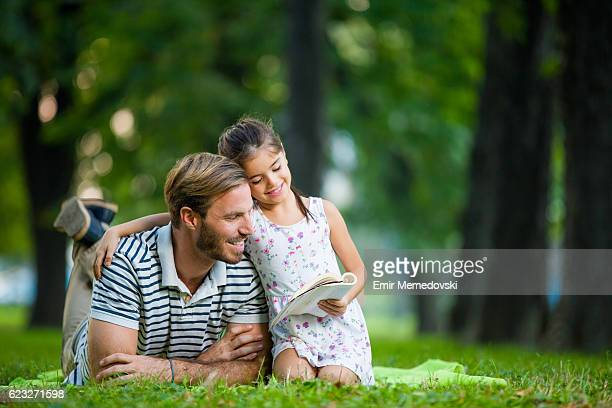 father and daughter reading a book in the park - lying on front stock pictures, royalty-free photos & images