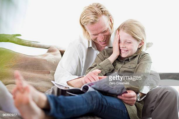 father and daughter reading a magazine