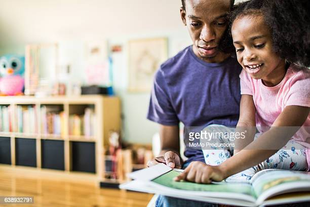 father and daughter reading at home - homeschool stock pictures, royalty-free photos & images