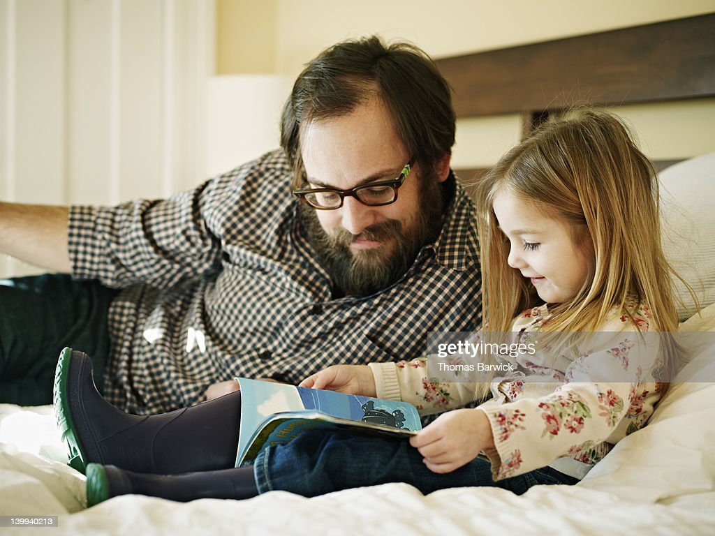 Father and daughter reading book in bed : Stock Photo