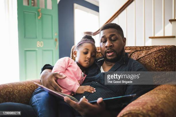 father and daughter reading book in living room at home - childhood stock pictures, royalty-free photos & images