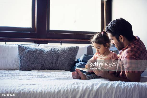 father and daughter reading book, lying on bed - genderblend stock-fotos und bilder
