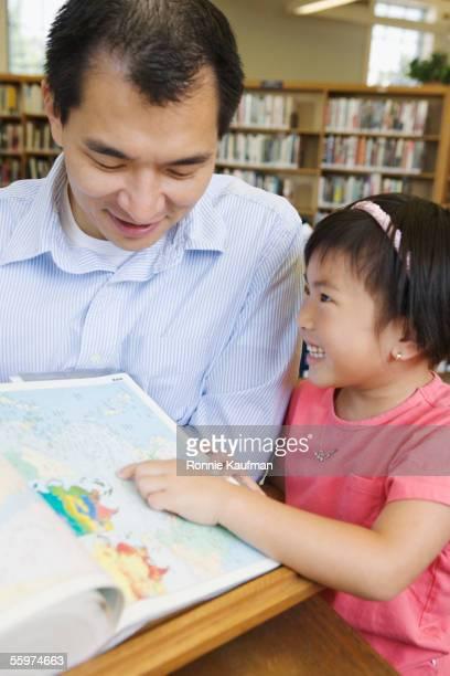 father and daughter reading books in library - enzyklopädie stock-fotos und bilder