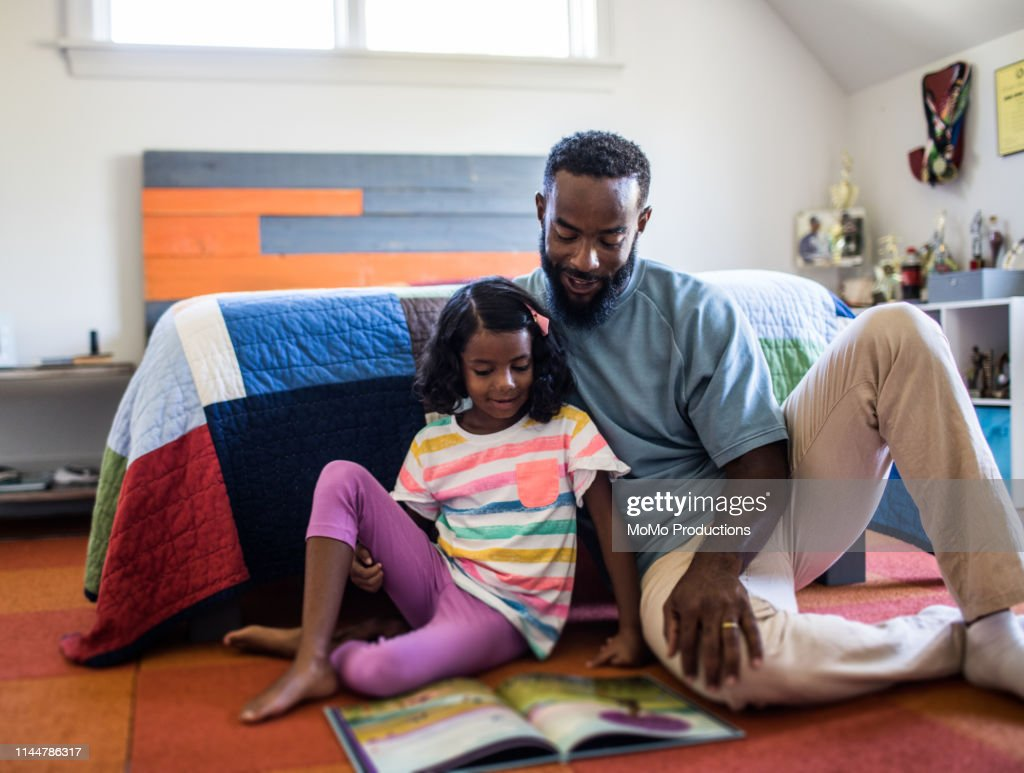 father and daughter reading in bedroom : Stockfoto