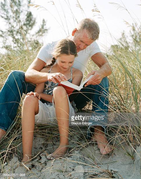 father and daughter (11-13) reading on beach, close-up - blasius erlinger stock pictures, royalty-free photos & images