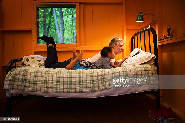 father and daughter reading on bed - contar histórias imagens e fotografias de stock