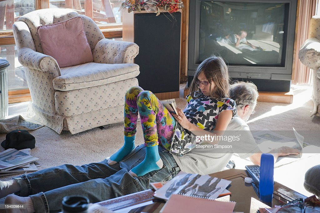Father and daughter reading on living room floor : Stock Photo