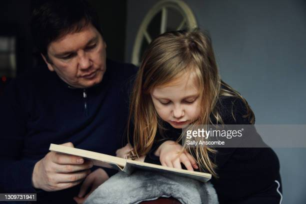 father and daughter reading together - sally anscombe stock pictures, royalty-free photos & images
