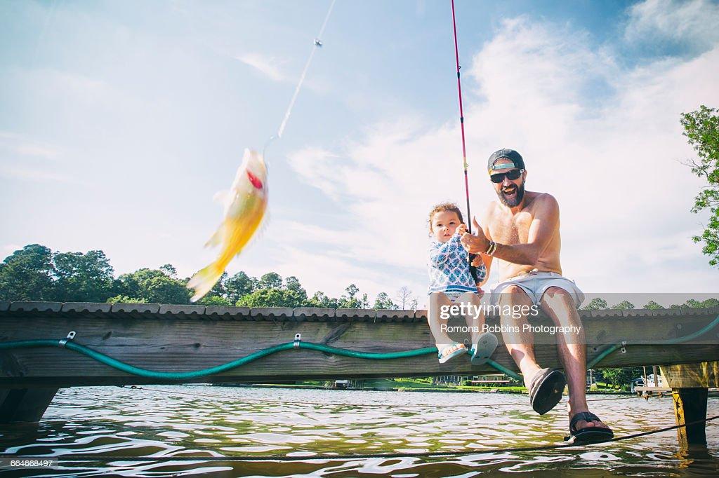 Father and daughter reeling in fish at Lake Jackson, Atlanta, Georgia, USA : Stock Photo