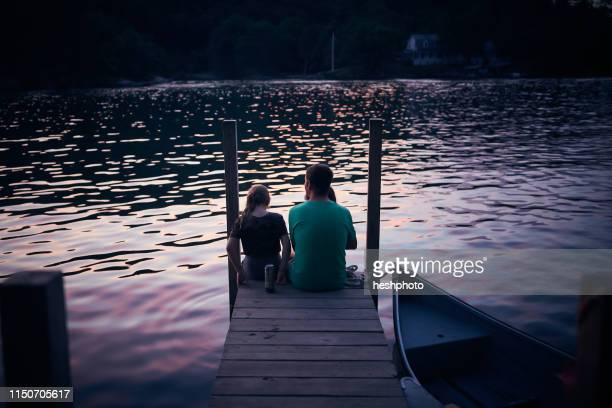 father and daughter relaxing at lake - heshphoto stock pictures, royalty-free photos & images