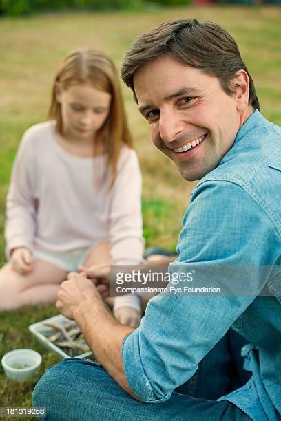 """father and daughter relaxing in garden - """"compassionate eye"""" stockfoto's en -beelden"""