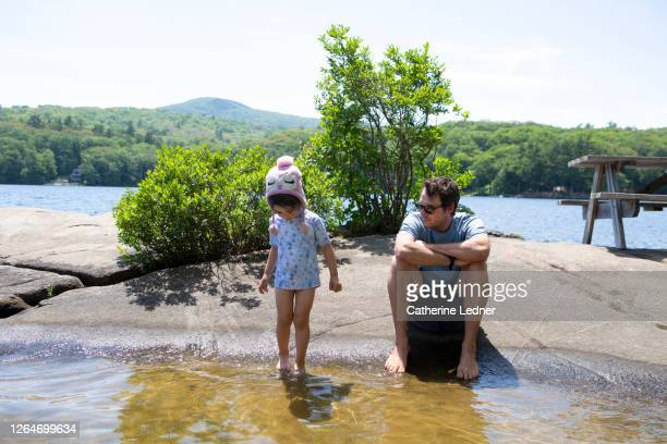 father and daughter relaxing on granite rock in the middle of a lake in maine - catherine ledner stock pictures, royalty-free photos & images