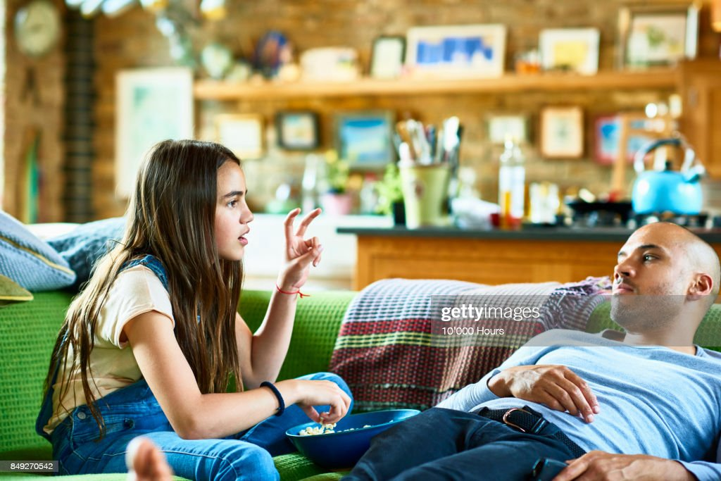 Father and daughter relaxing on sofa : Stock Photo