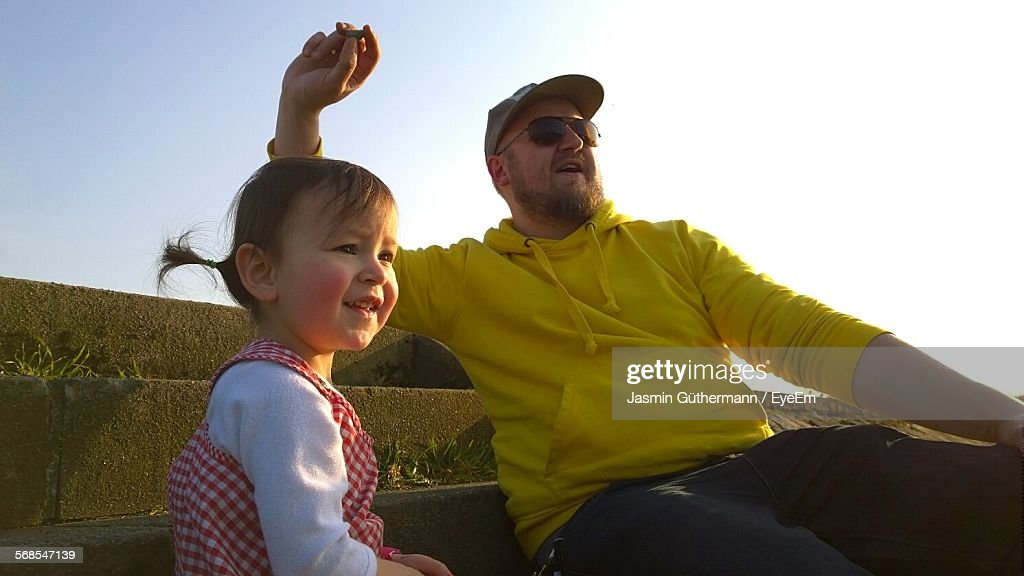 Father And Daughter Relaxing On Steps : Stock Photo