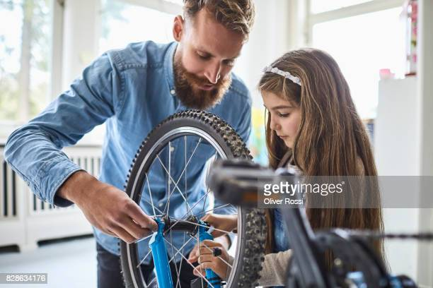 father and daughter repairing bicycle at home - leanincollection stock pictures, royalty-free photos & images